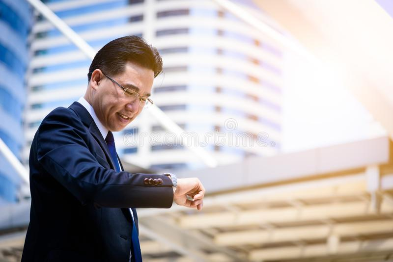 The asian businessman has holding a black bag and looking on watch in hurrying time. stock images