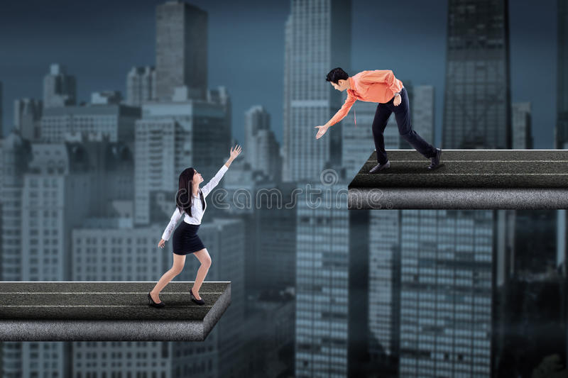 Asian businessman helping a businesswoman stock images