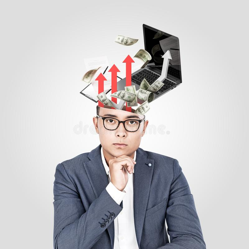 Asian businessman and his business plan. Serious young Asian businessman in glasses sitting near gray wall with laptop, money and graphs emerging from his head stock images