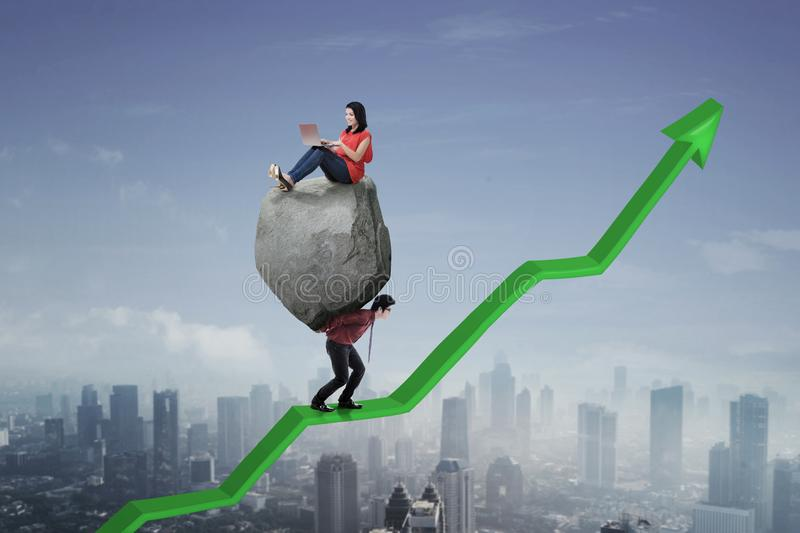 Asian businessman with his leader and upward arrow. Image of Asian businessman lifting a stone with his leader using a laptop while walking on an upward arrow royalty free stock image