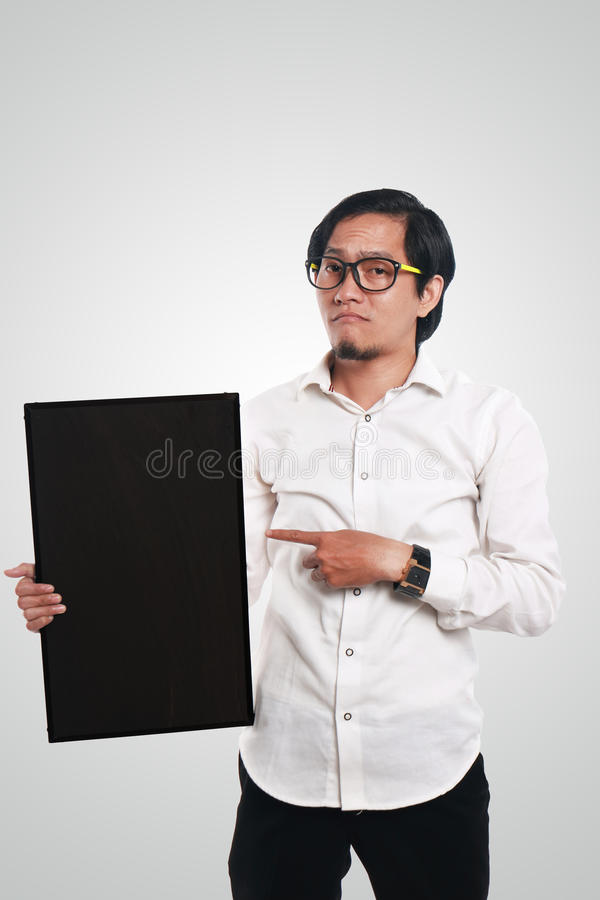 Asian Businessman Holding Blackboard. Photo image portrait of funny Asian businessman or teacher or student showing empty blackboard with sad face, holding royalty free stock image