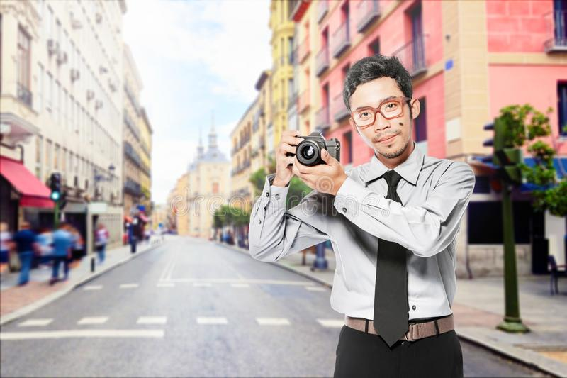 Asian businessman holding the camera on his hand standing royalty free stock images