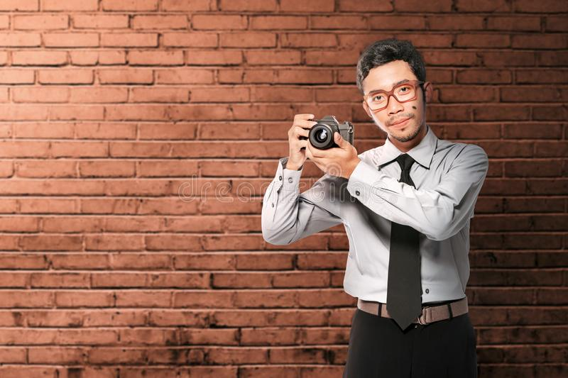 Asian businessman holding the camera on his hand standing stock photo
