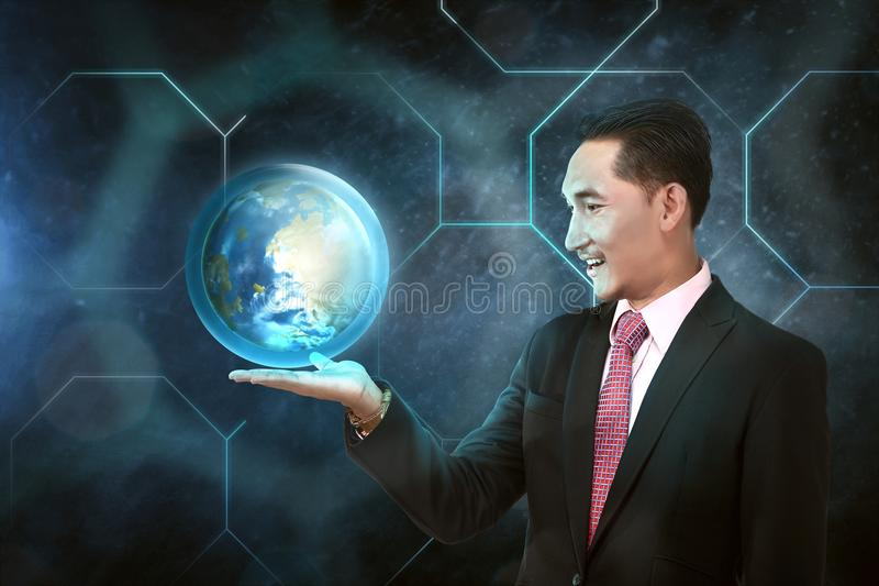 Asian businessman holding earth planet on his hand royalty free stock photography