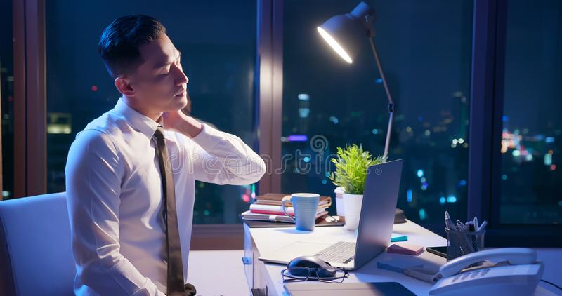 Businessman overtime work. Asian businessman overtime work and feel neck pain in the office royalty free stock photos