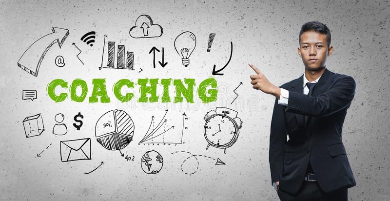 Asian Businessman Pointing `Coaching` Text Sketch Concept.  stock photos