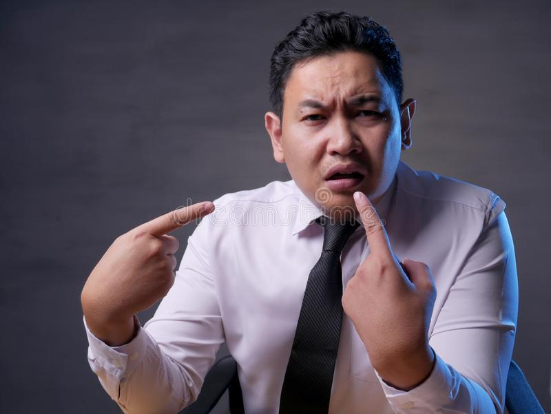 Asian Businessman Pointing Himself with Unhappy Expression as if he confused to be accused. Asian mbusinessman pointing himself with unhappy displeased royalty free stock photo