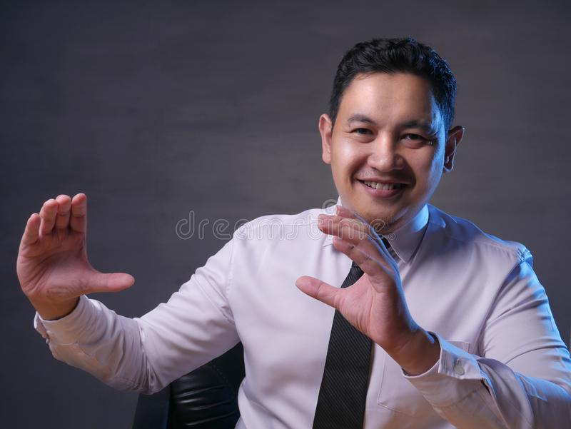 Asian Businessman Presenting Something on His Side with Copy Space stock photography