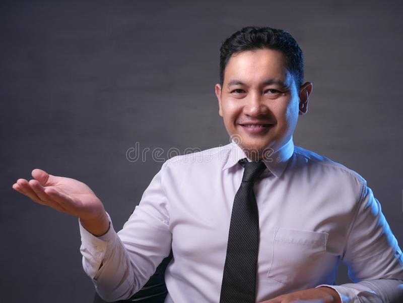 Asian Businessman Presenting Something on His Side with Copy Space royalty free stock photography