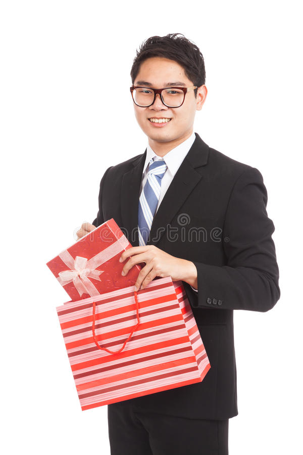 Asian businessman pull gift box from shopping bag. Asian businessman pull red gift box from red shopping bag isolated on white background stock images