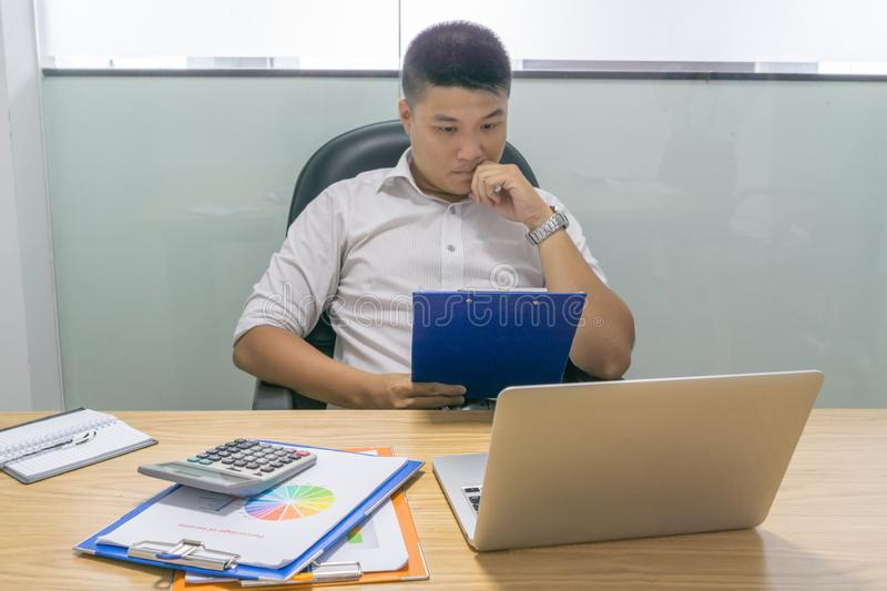 Asian businessman reading financial report document stock photography