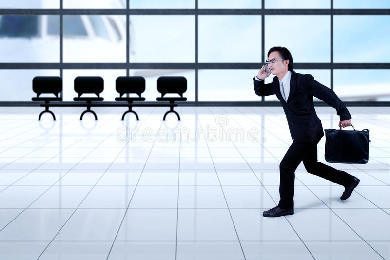 Asian businessman running in the airport royalty free stock image