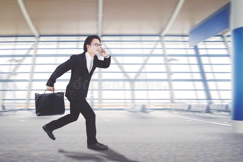 Asian businessman is running in the arrival hall stock photography