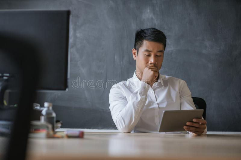 Asian businessman sitting at his desk working on a tablet. Focused young Asian businessman working on a digital tablet while sitting at his desk in front of a royalty free stock photo