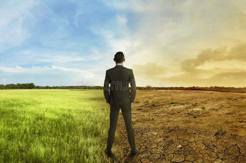 Asian businessman standing between different climate. On the daylight royalty free stock photo