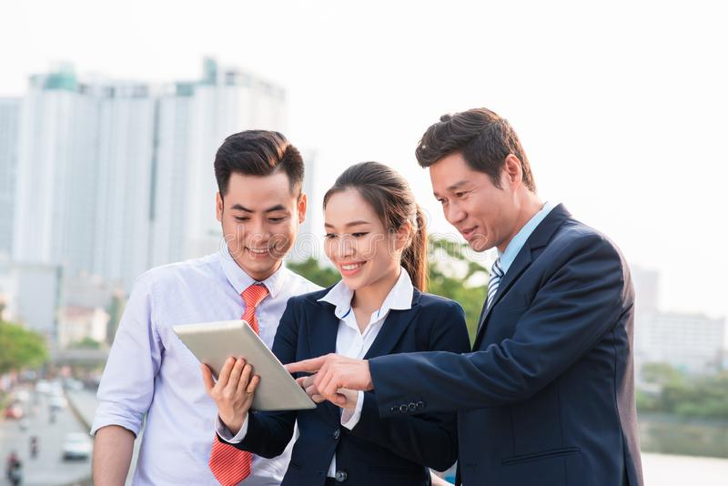 Asian businessman in suit showing online presentation on digital tablet to his colleagues while they standing stock images