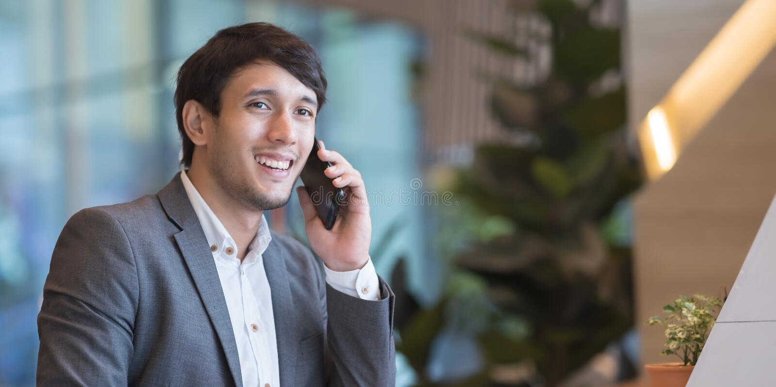 Asian businessman in suit speaking on the phone in office. royalty free stock image