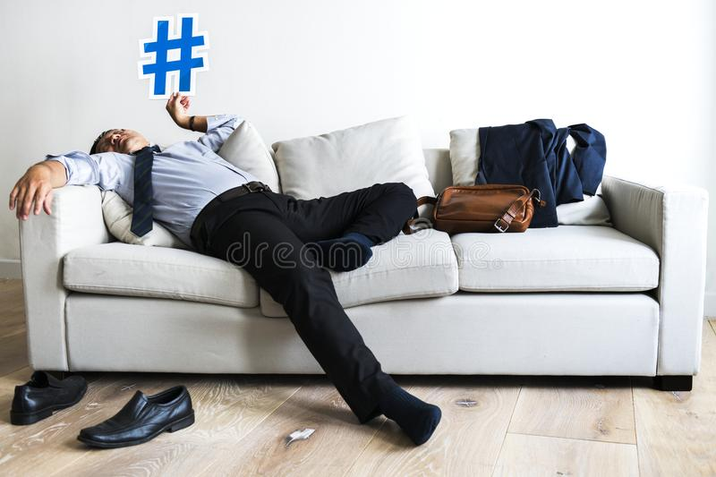 Businessman taking break laying on couch royalty free stock photos