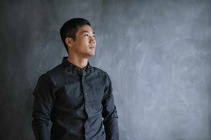 Asian businessman thinking while standing in front of a chalkboard stock image