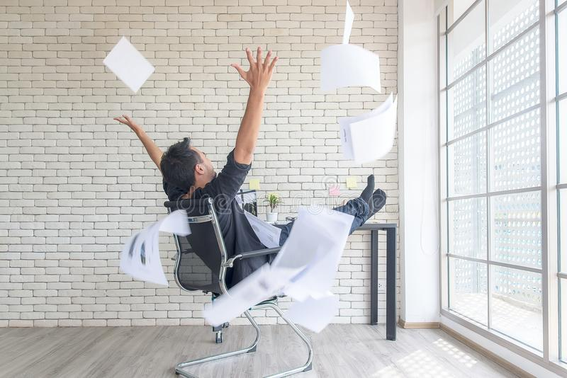 Asian businessman tossing a bunch of papers celebrating the end of his work and success report. He relax and happy with your work. Business Concept royalty free stock photography