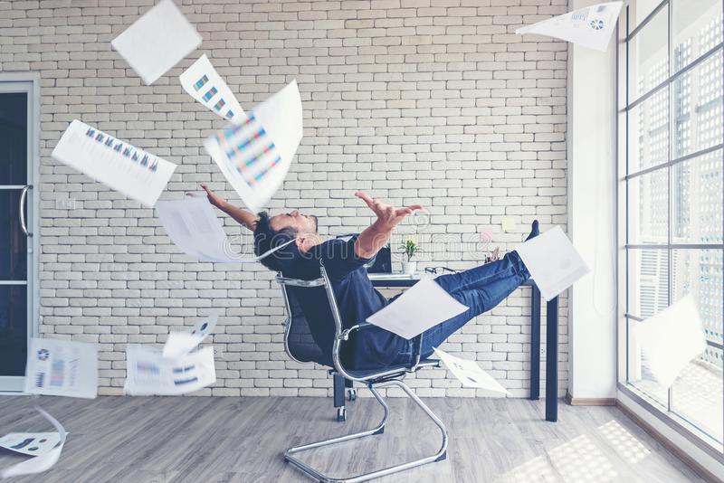 Asian businessman tossing a bunch of papers celebrating the end of his work and success report. He relax and happy with your work. Business Concept royalty free stock image