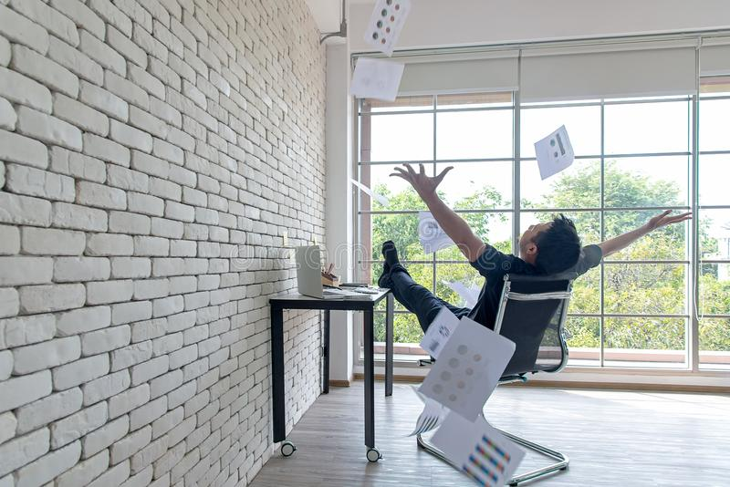 Asian businessman tossing a bunch of papers celebrating the end of his work and success report. He relax and happy with your work. Business Concept royalty free stock photos