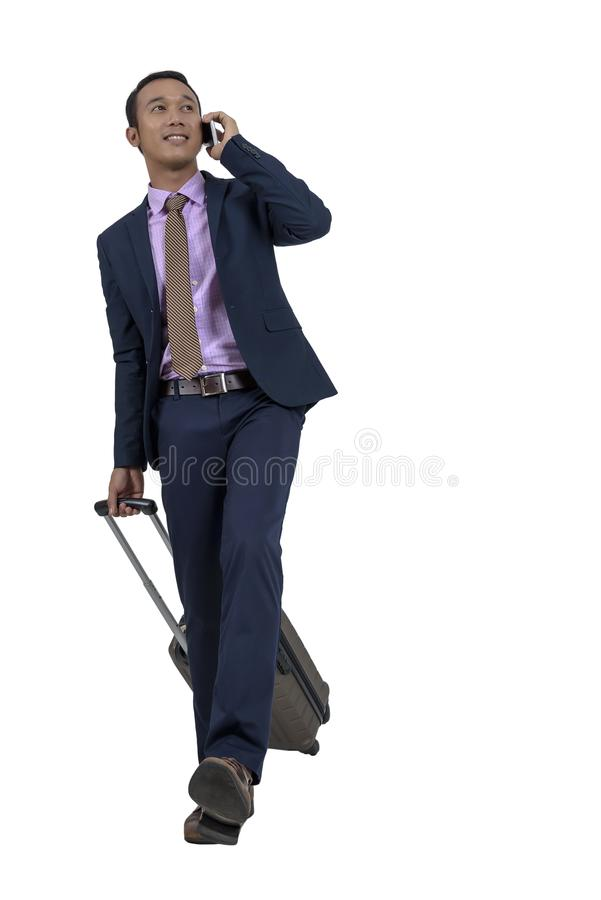 An Asian businessman is traveling with luggage and a smartphone. royalty free stock photos