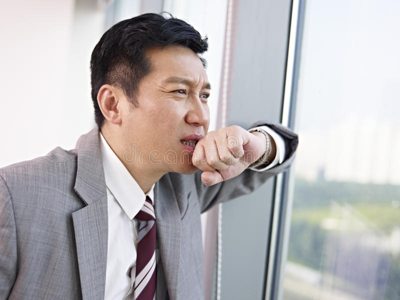 Asian businessman. Troubled asian businessman looking out of window and thinking in office stock image