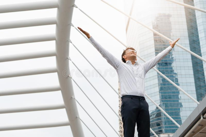 Asian businessman in urban raising his hands with open palmsand looking up to sky feeling happyand success royalty free stock photo
