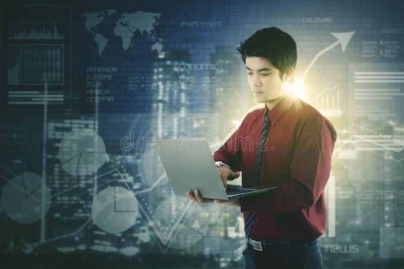 Asian businessman using laptop against a futuristic HUD interface screen. Asian businessman using laptop with a futuristic HUD interface screen with data and key royalty free stock image
