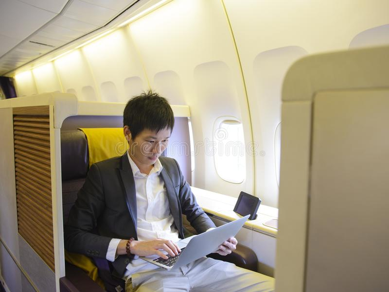 Asian businessman using laptop on first class airplane.  royalty free stock photography