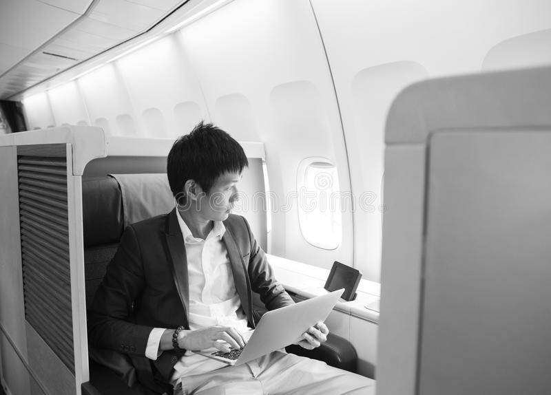 Asian businessman using laptop on first class cabin.  stock image