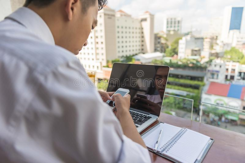 Young Asian businessman using smartphone on the balcony royalty free stock image