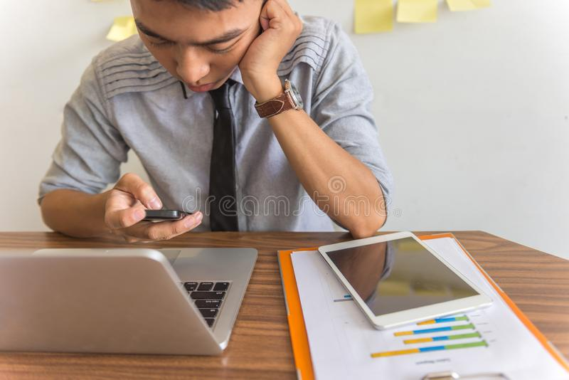 Asian businessman using smartphone and laptop in the office stock photo