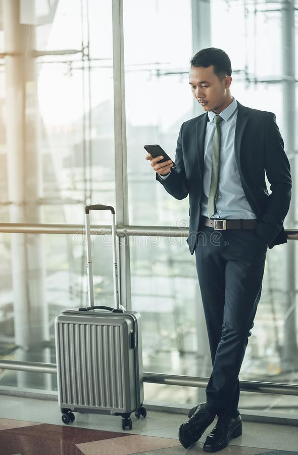 An Asian businessman is using a smartphone to get in business while waiting for a trip in the airport. royalty free stock images