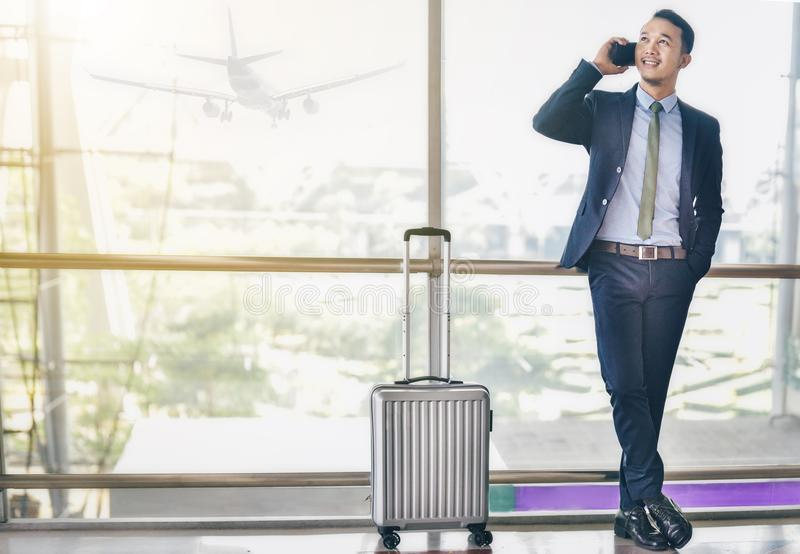 An Asian businessman is using a smartphone to get in business while waiting for a trip in the airport. stock photography