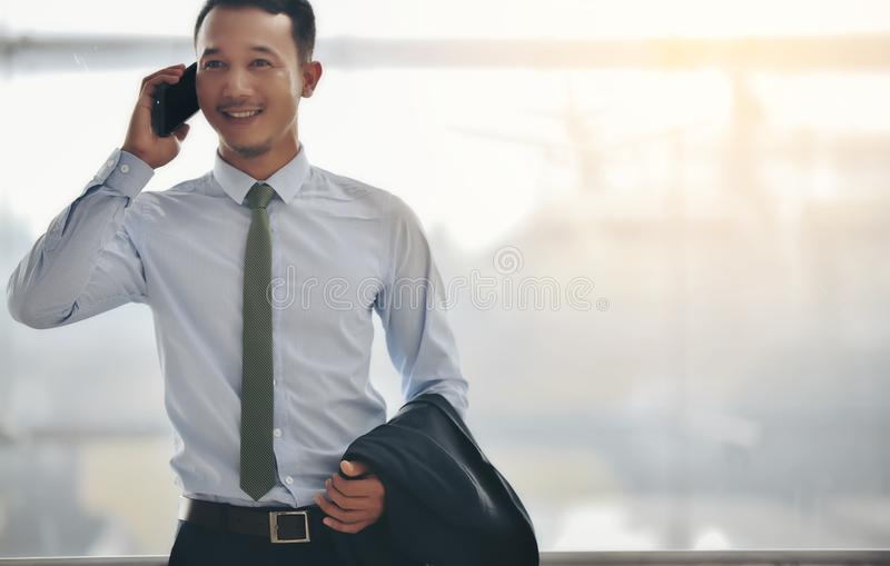 An Asian businessman is using a smartphone to get in business while waiting for a trip in the airport. royalty free stock photography