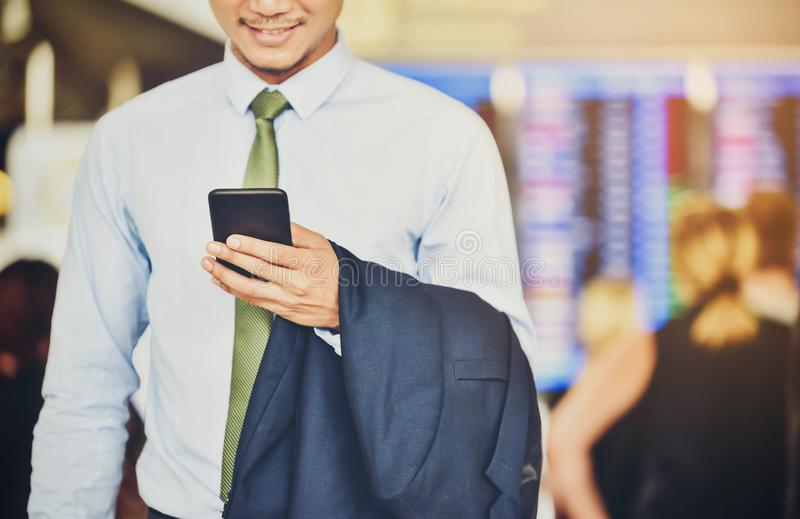 An Asian businessman is using a smartphone to get in business while waiting for a trip in the airport. stock photos