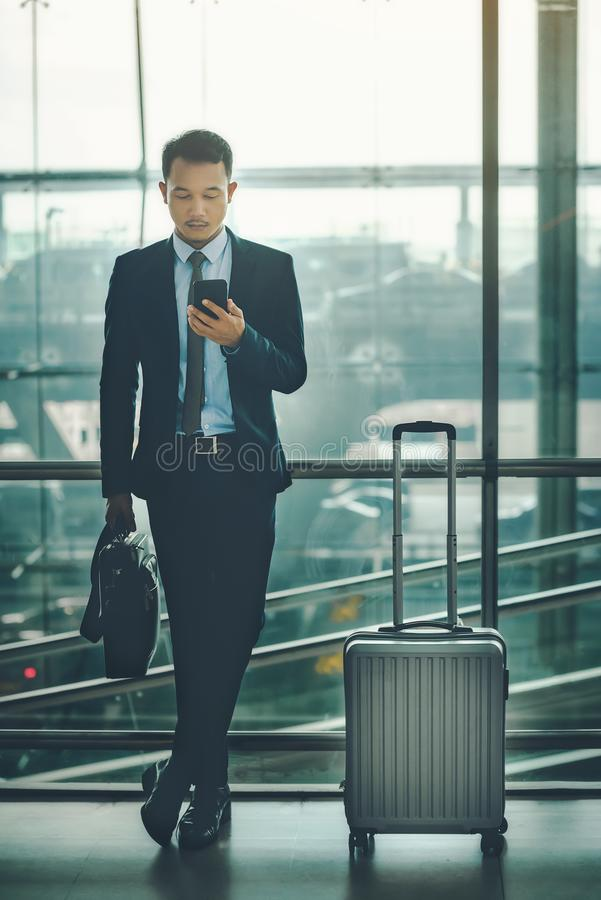 An Asian businessman is using a smartphone to get in business while waiting for a trip in the airport. stock images