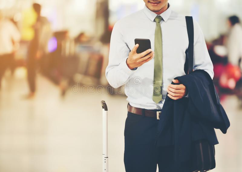 An Asian businessman is using a smartphone to get in business while waiting for a trip in the airport.This image is Soft focus. royalty free stock images
