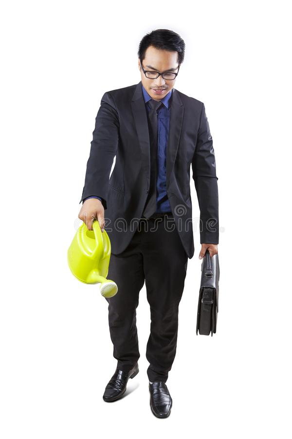 Asian businessman using a watering can stock photos