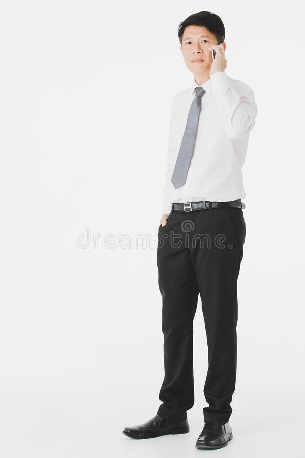 Asian businessman, in white shirt holding use calling smartphone. Portrait of middle aged, handsome, Asian, businessman, in white shirt, striped tie.posing royalty free stock images