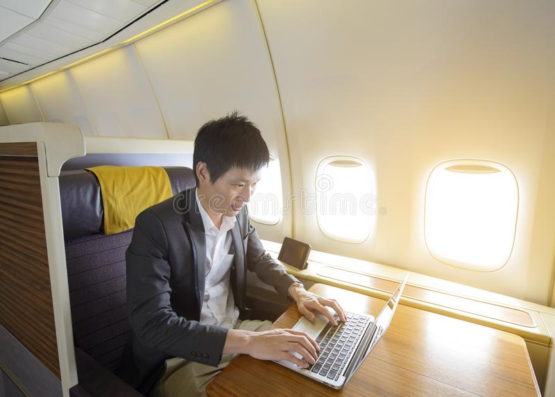 Asian businessman working on laptop in the luxury airplane stock images