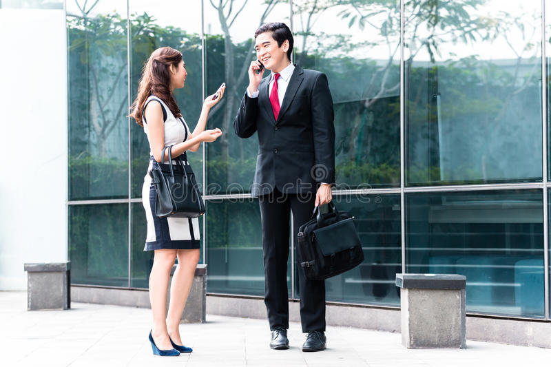 Asian businesspeople talking to cell phones outside stock images