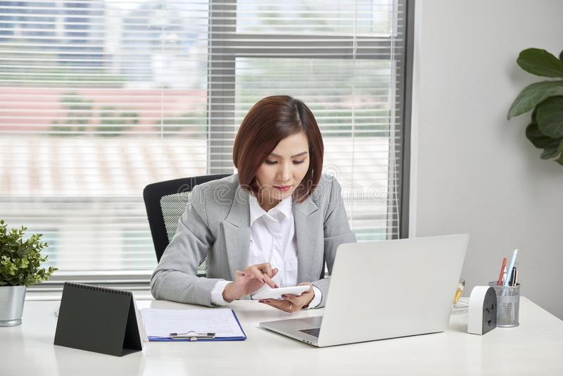 Asian businesswoman or accountant working pointing graph discussion and analysis data charts and graphs and using a calculator to royalty free stock photo