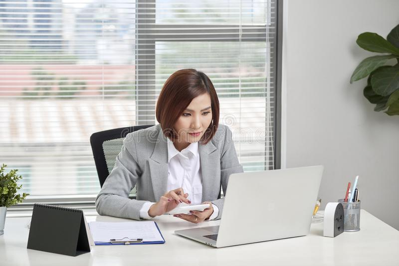 Asian businesswoman or accountant working pointing graph discussion and analysis data charts and graphs and using a calculator to royalty free stock image
