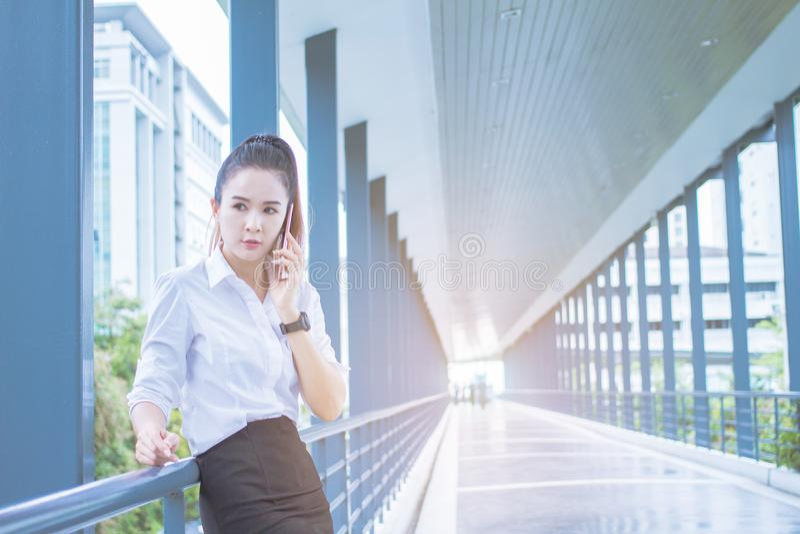 Asian Businesswoman call phone talking , Meetings between executives. between waiting on On sidewalks. Asian Businesswoman call phone talking , Meetings between stock photos