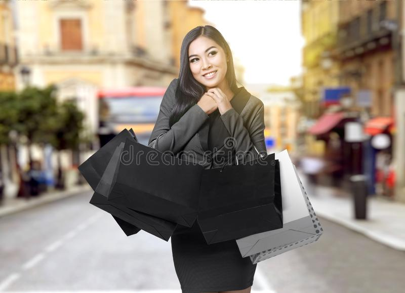 Asian businesswoman carrying shopping bags in the city stock photography