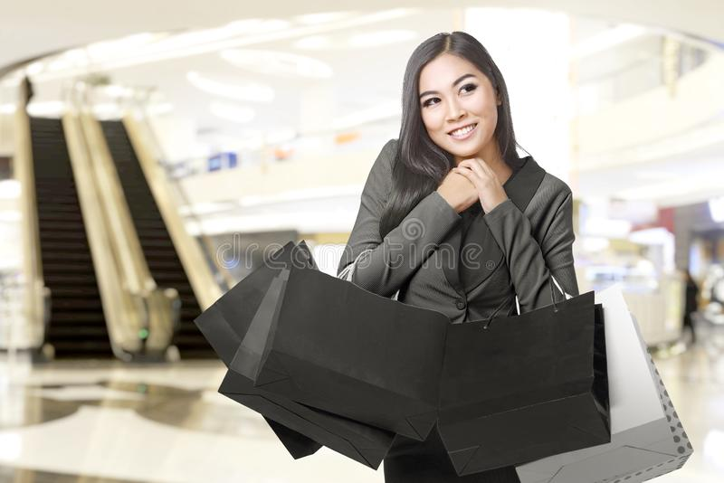 Asian businesswoman carrying shopping bags in the mall royalty free stock photo