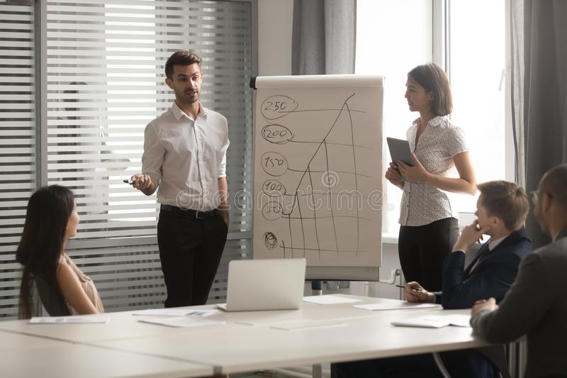 Asian businesswoman and Caucasian businessman making flip chart presentation royalty free stock photography